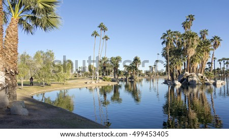 Bright and clear winter sky reflecting in deep blue water of Encanto park lake, Phoenix downtown, Arizona; Copyspace