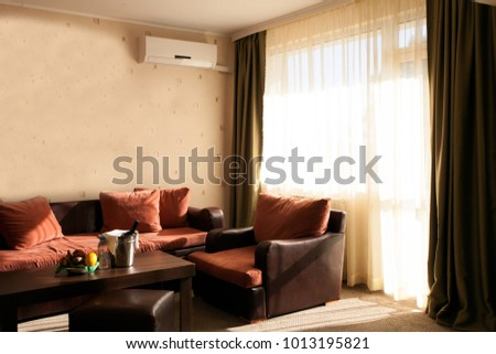 Bright and cozy modern livingroom in the hotel , large window and broad window sill for read with soft seats and cushions