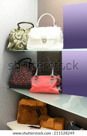 bright and fashionable interior of bag store in modern mall - stock photo