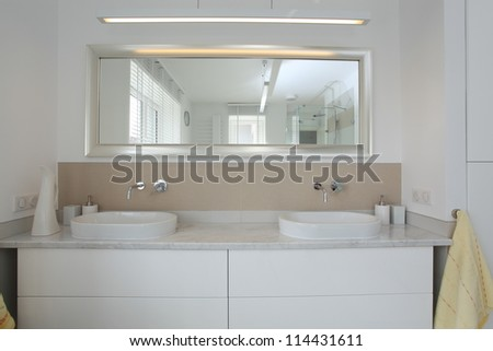 Bright and modern bathroom, sink and mirror - stock photo