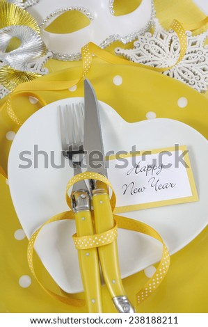 Bright and modern yellow and white theme Happy New Year table with heart shape plate on polka dot place setting. Vertical closeup.