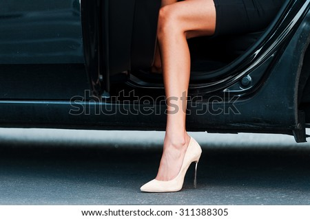 Bright appearance. Close-up of young businesswoman wearing heels while coming out her car