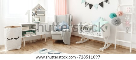 Bright Armchair With Blanket And Cushion Standing Next To White Wooden  Cradle In Pastel Baby Room
