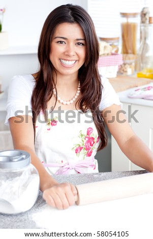 Bright asian woman baking in the kitchen smiling at the camera - stock photo