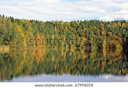 Bright autumn trees with their reflection in water - stock photo
