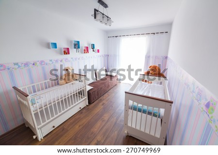 Bright baby room with pastel wallpapers and white cradles - stock photo