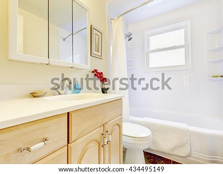 Bright bathroom interior with wooden cabinets, mirror and toilet.