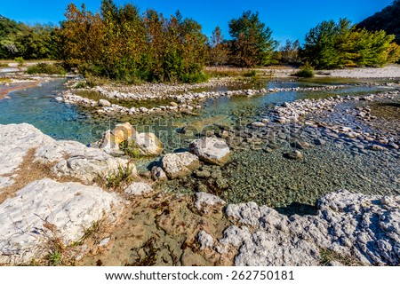 Bright Beautiful Fall Foliage on the Gravely Crystal Clear Frio River of Texas - stock photo