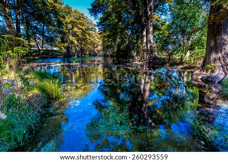 Bright Beautiful Fall Foliage Reflecting on the Crystal Clear Frio River.  Texas. - stock photo