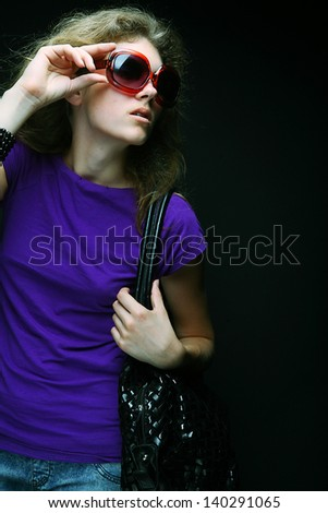 bright beautiful young woman with fashion sunglasses and handbag - stock photo
