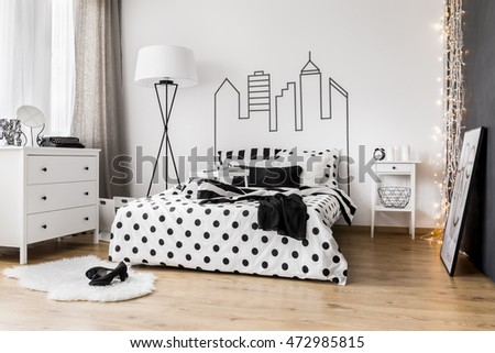 Bright bedroom interior with wide bed, commode and bedside cabinet