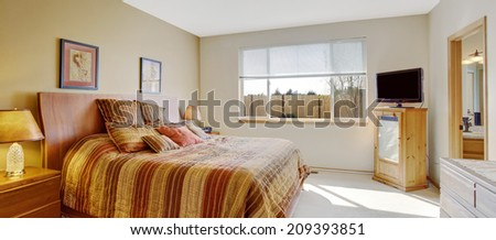 Bright bedroom with cheerful orange striped bed and tv - stock photo