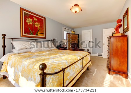 Bright bedroom with rustic wooden cabinets, iron frame bed, wicker chair and wicker privacy screen - stock photo