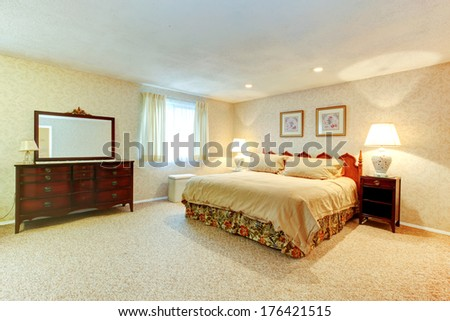 Bright bedroom with soft carpet floor, beige wallpapers. Room furnished with antique queen size bed, big cabinet with mirror and nightstand.