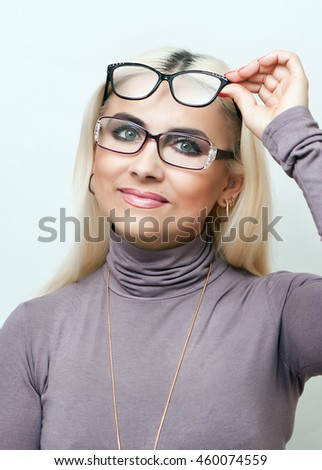 Bright blonde tries on glasses - stock photo