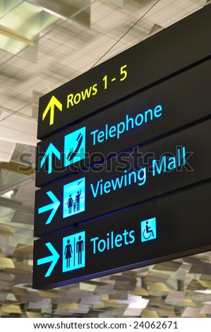 Bright blue and yellow directional signs in airport - stock photo
