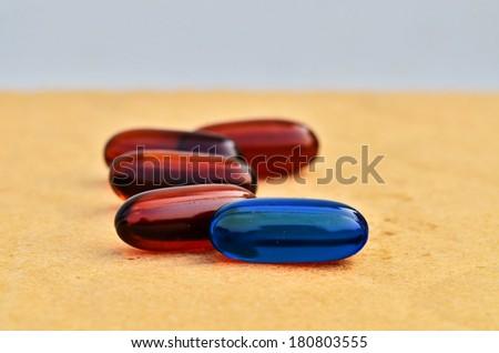 Bright blue capsules in brown capsules - stock photo