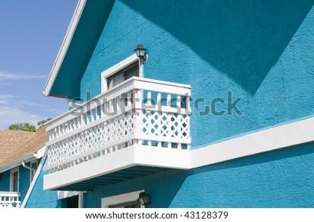 Bright blue colored Abandon condominium with white lattice balcony due to recession - stock photo