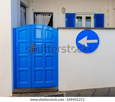 Bright blue door on a white house wall on Stromboli island, Sicily, Italy. - stock photo
