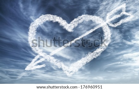 Bright blue dramatic sky with cloudy heart and arrow - love concept