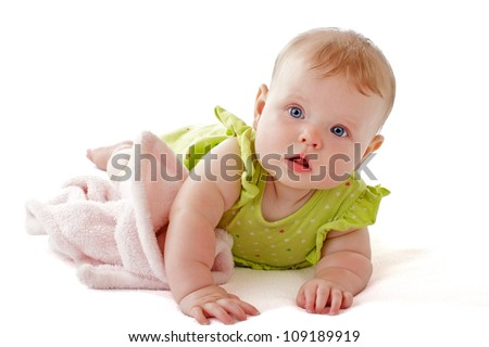 Bright blue eyed 6 month old baby girl in lime green dress on her tummy with a soft blanket. Horizontal, isolated on white background, copy space.