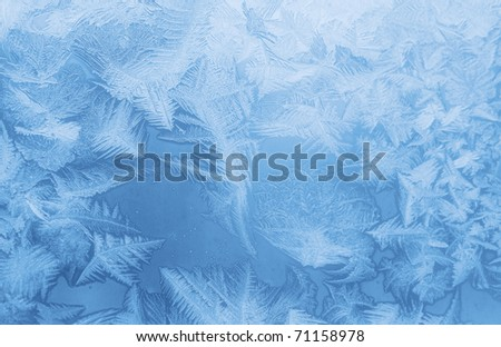 Bright blue frost pattern on a window glass (as an abstract winter background) - stock photo