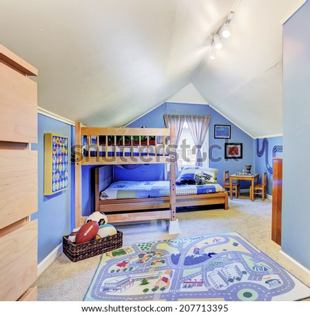 Bright blue kids room with vaulted ceiling. Furnished with bunk bed and table set - stock photo