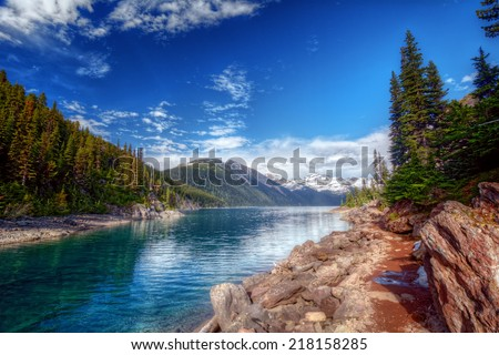 Bright blue mountain creek with a path along the shore and scenic trees and mountains