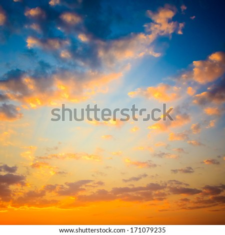 Bright Blue, Orange And Yellow Colors Sunset Sky. Sunlight through clouds - stock photo