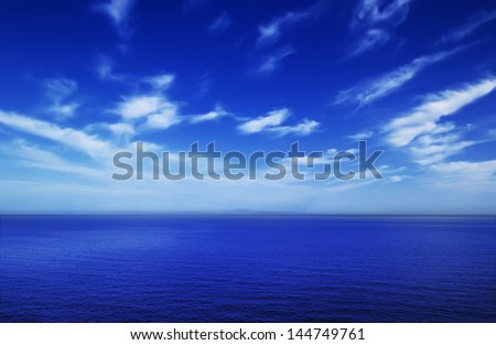 Bright blue sea and sky with fluffy clouds, running into the distance in the Crimea, Ukraine - stock photo