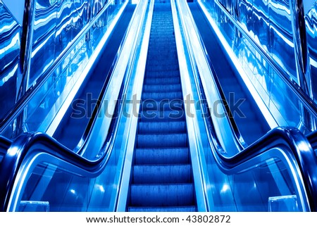 bright blue steps of moving escalator in airport - stock photo