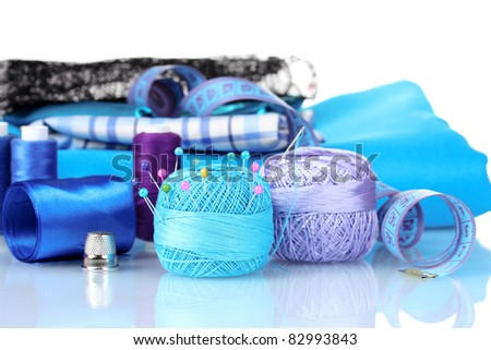 bright blue yarn, fabric, satin ribbon and measuring tape isolated on white