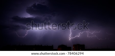 Bright branched lightning over the rooftops of urban buildings - stock photo