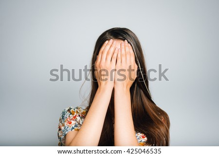 bright brunette girl covers her face with her hands, isolated on a gray background - stock photo