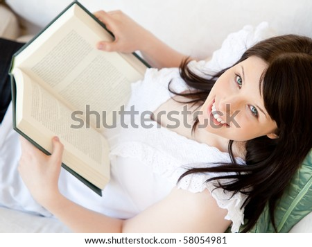 Bright brunette teenager holding a book smiling at the camera in the living room - stock photo