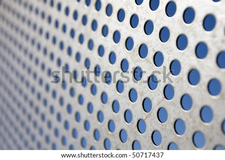 Bright brushed and drilled a hole metal texture over a blue background (selective focus, photographed with shallow DOF) - stock photo