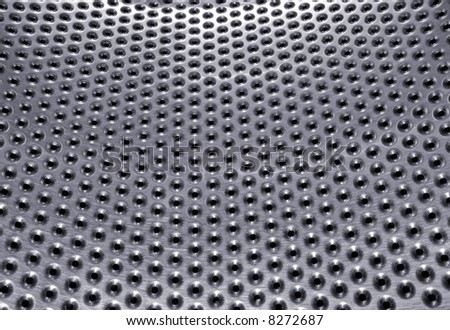 Bright brushed and perforated metal surface details - stock photo
