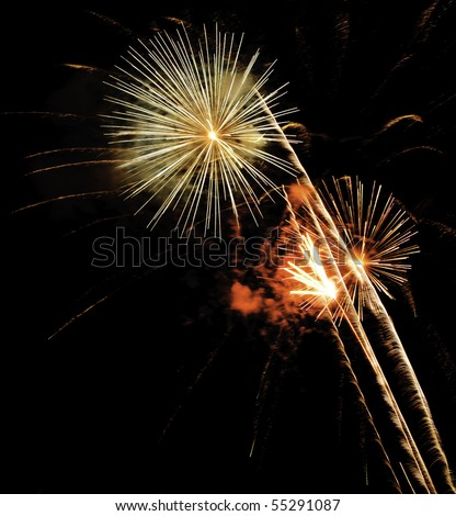 Bright bursts of fireworks with rocket trails and reddish and greenish puffs of smoke - stock photo