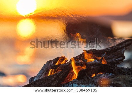 Bright campfire on the beach in evening - stock photo