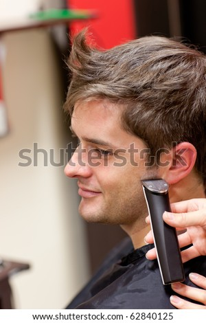 Bright caucasian man being shaved in a hairdressing salon - stock photo