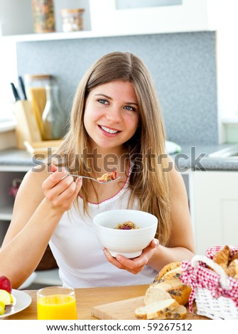 Bright caucasian woman eating cereals with strawberries sitting in the kitchen