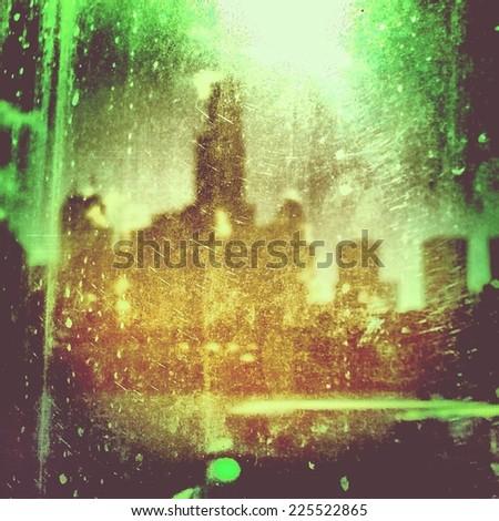 Bright city lights and shadows through a foggy window. - stock photo