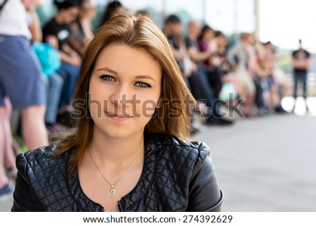 Bright close-up portrait of a popular university student girl with her followers in the background. She is a team leader! - stock photo