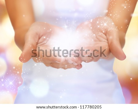 bright closeup picture of magic twinkles on female hands - stock photo