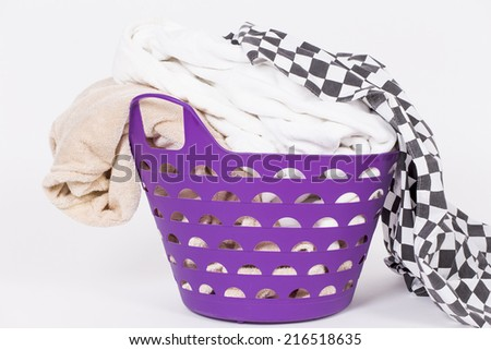 Bright clothes in a laundry basket on white background. - stock photo