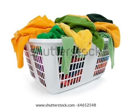 Bright clothes in a laundry basket on white background. Green, yellow. - stock photo
