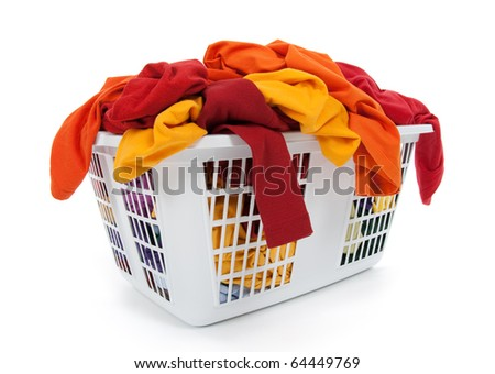 Bright clothes in a laundry basket on white background. Red, orange, yellow. - stock photo