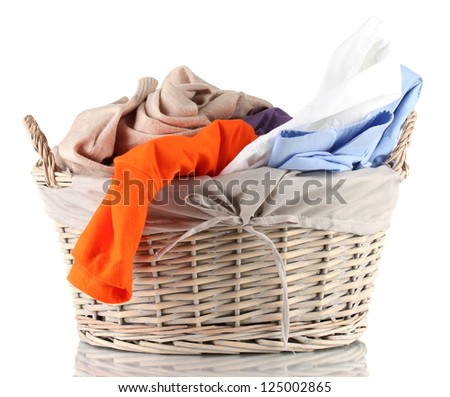 Bright clothes in laundry basket, isolated on white - stock photo