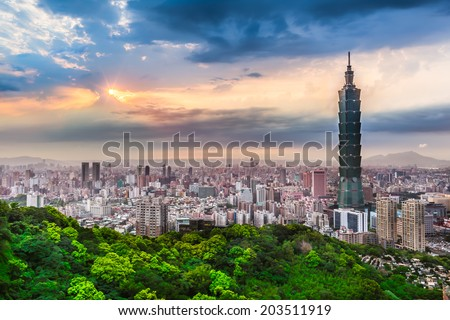 Bright cloudy sky at an spring evening with sunshine rays and wide cityscape of Taipei, Taiwan/Taipei City View at Evening - stock photo