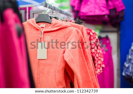 Bright color fluff jackets for girls in supermarket - stock photo